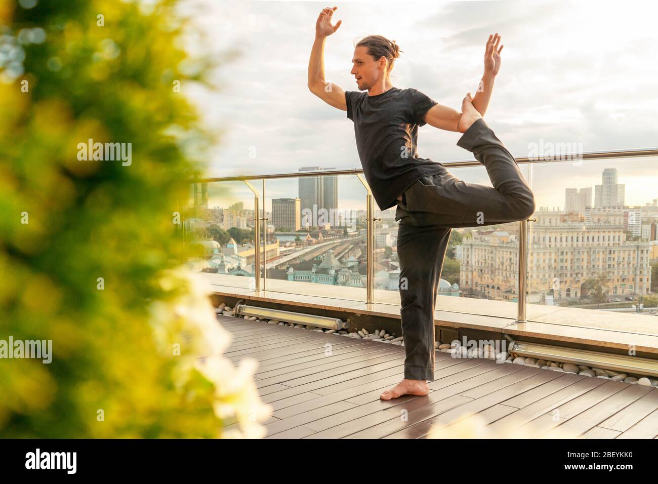 Man In Harmony With Himself Meditating And Relaxing on His Roof with Beautiful View on City. Catching Zen From Stress made by Coronavirus Pandemia and Stock Photo