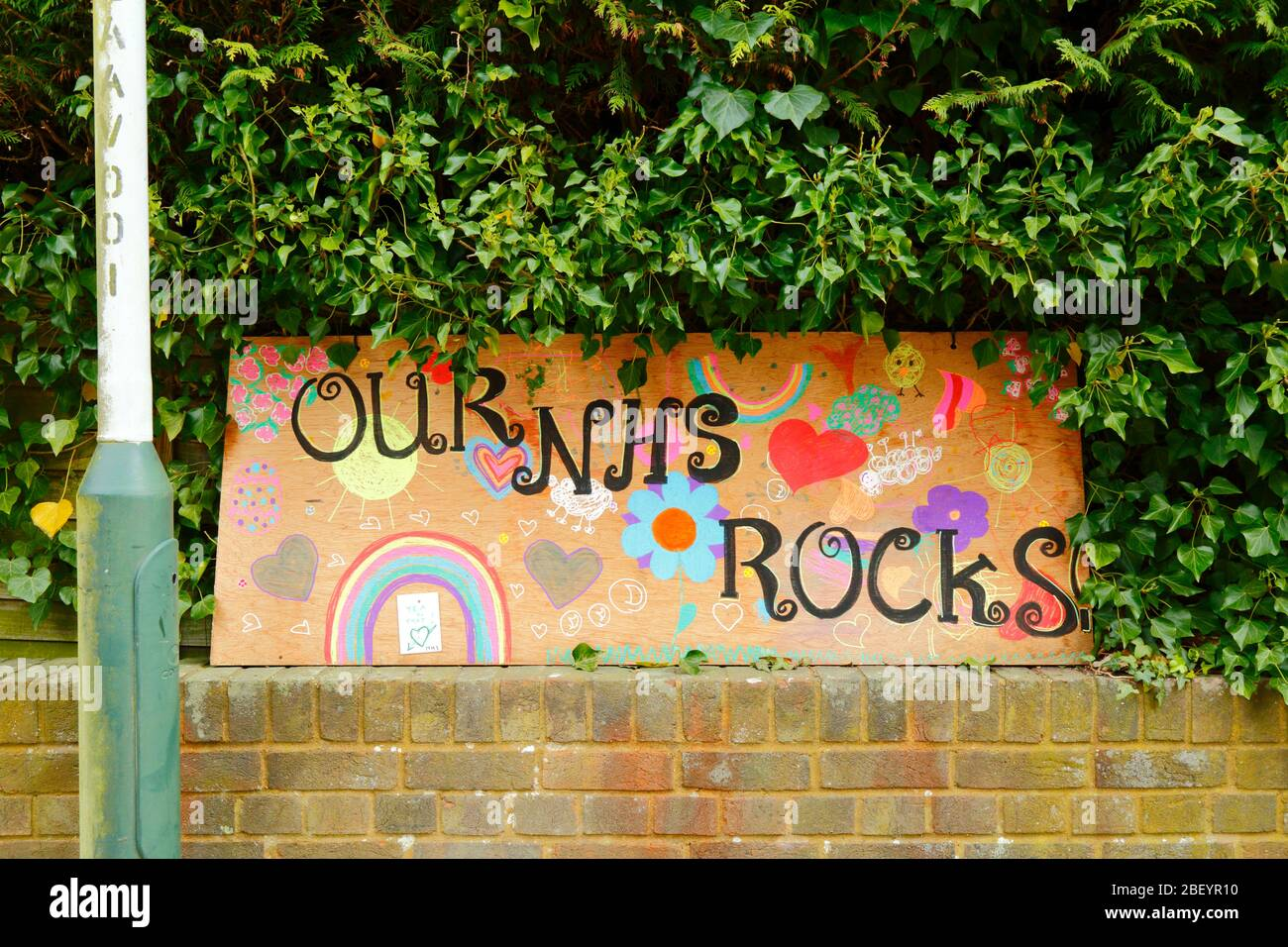 16th April 2020, Southborough, Kent, UK: Child's drawings of a rainbow, hearts and Our NHS Rocks message for NHS staff and key workers on a plywood board outside a hedge in residential area during the government imposed quarantine / lockdown to reduce the spread of the coronavirus. Children across the country have been putting drawings of rainbows in windows to spread hope and encourage people to stay cheerful during the pandemic. Stock Photo