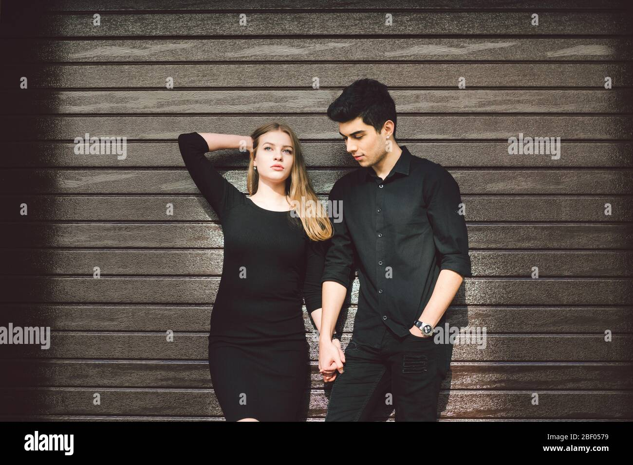 Multiracial stylish couple in black clothes posing on a background of a wooden wall. Turkish guy and caucasian woman date and love. Lifestyle Stylish Stock Photo