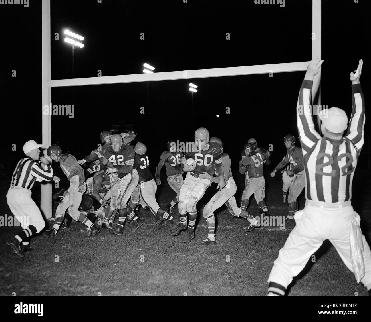1950s NIGHT 9/16/1950 FIRST NFL FOOTBALL GAME PHILADELPHIA EAGLES VS CLEVELAND BROWNS OTTO GRAHAM SCORING TD PHILADELPHIA PA USA - f683 HAR001 HARS ATHLETICS COPY SPACE FULL-LENGTH PERSONS INSPIRATION MALES ATHLETIC PROFESSION ENTERTAINMENT NUMBERS PLAYERS B&W SUCCESS WIDE ANGLE SKILL OCCUPATION SKILLS UMPIRE VICTORY EAGLES CAREERS EXCITEMENT PA OCCUPATIONS UNIFORMS PROFESSIONAL SPORTS CLEVELAND CONNECTION GOAL POST VS ATHLETES SCORING TOUCHDOWN FOOTBALLS MID-ADULT MID-ADULT MAN PRO TOGETHERNESS VS. YOUNG ADULT MAN AMERICAN FOOTBALL BLACK AND WHITE HAR001 OLD FASHIONED Stock Photo