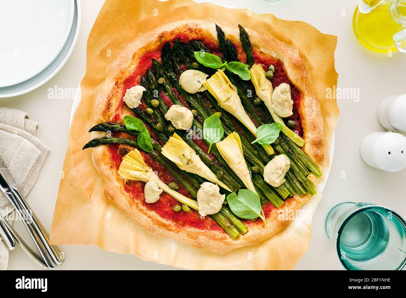 vegan pizza with asparagus and artichokes, served on the table for family or friends. Healthy lunch or dinner. Stock Photo