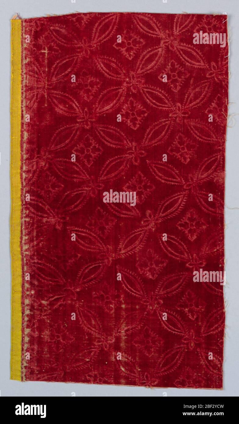 Fragment. Lattice framing four-petaled flowers on red velvet. Wide yellow selvage. Stock Photo