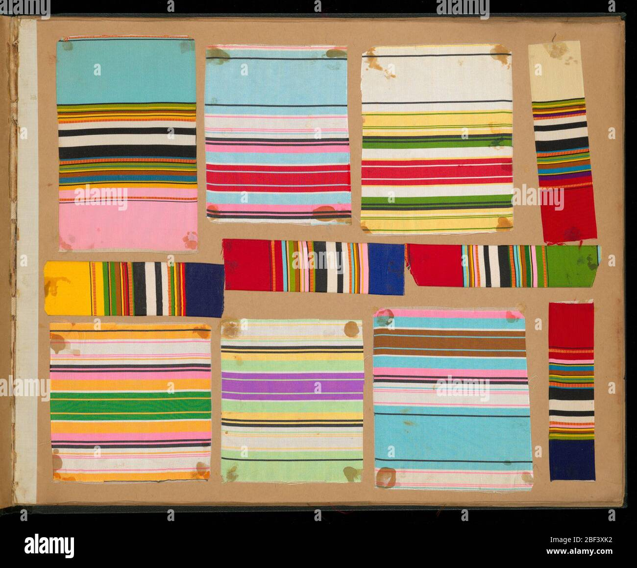 Sample book of woven ribbons. Sample book has 94 ribbon samples with stripes in various colors: 288 checks, 243 samples in plain cloth, moiré, chiné, and rep; 92 with fancy woven border; 11 with short fringes; 100 with jaquard weaves; 2 woven labels; 3 small flags. Stock Photo