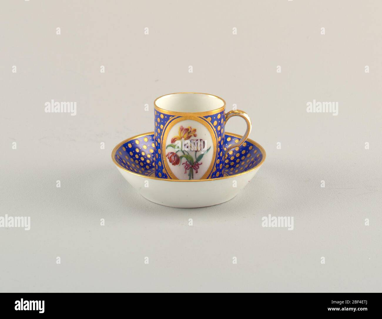Cup and saucer. Short, cylindrical cup (a) with scroll handle; enamel and gilded decoration consisting of gilt dots picked out in black, on blue ground; large, central, gilt-bordered oval cartouch with spray of three tulip blooms (red/cream, yellow/red, purple/cream) tied wit Stock Photo