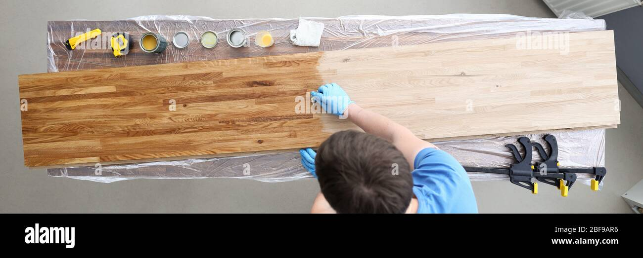 Woodworker varnishing surface Stock Photo