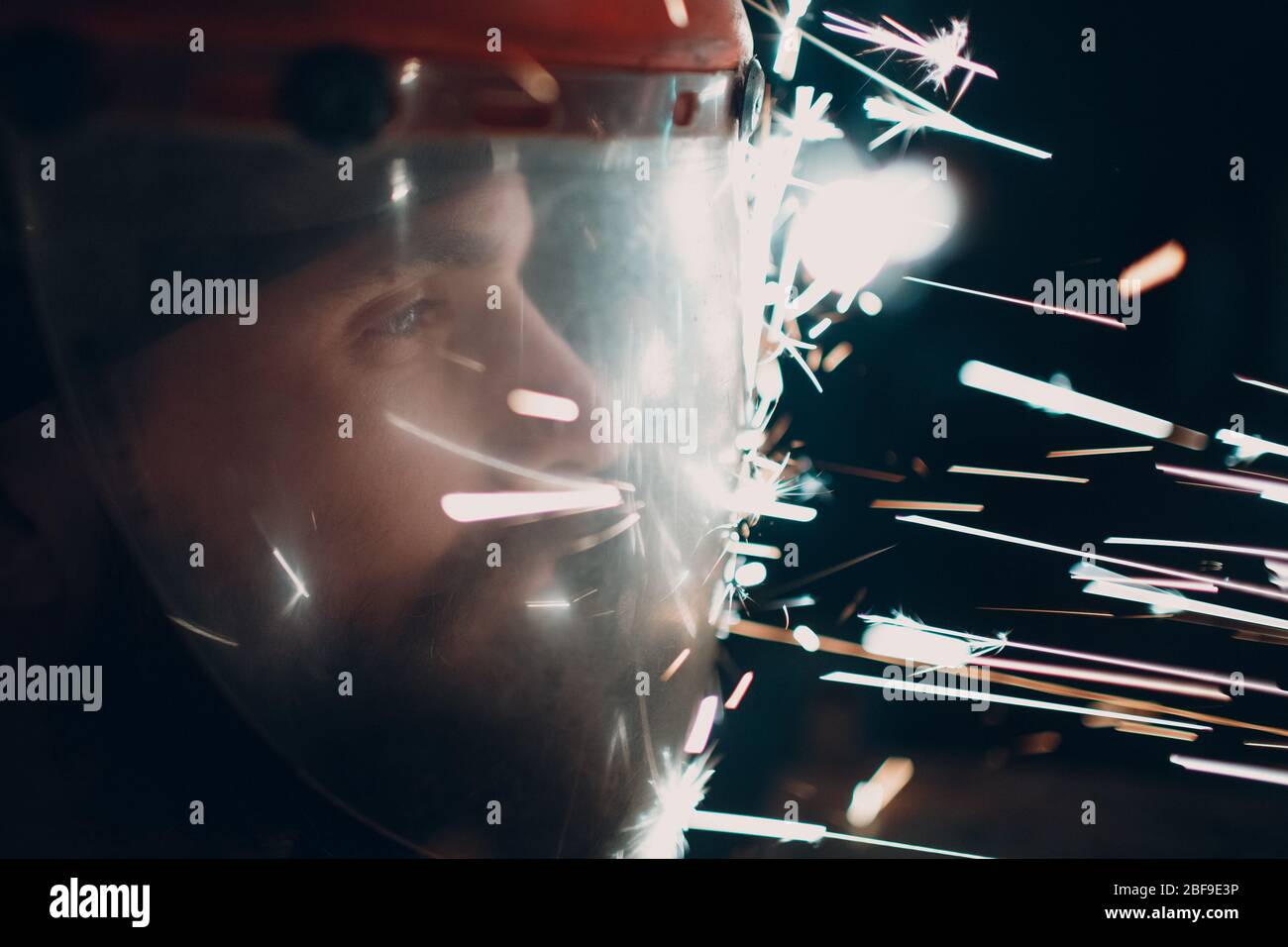 Adult bearded man in transparent protective mask with flying metal particles sparks in darkness Stock Photo