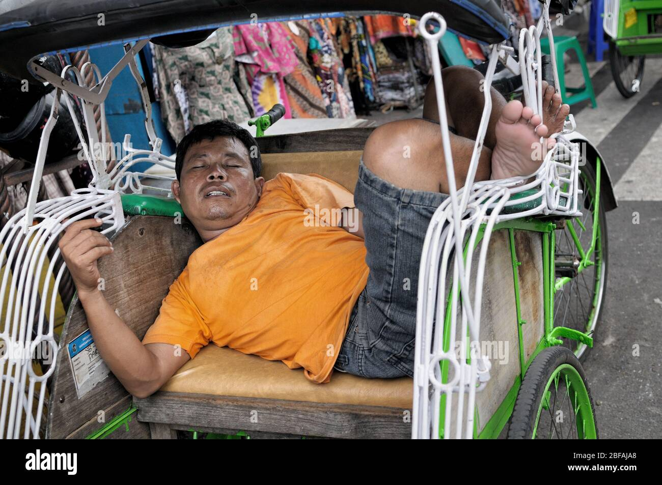Man sleeping in his cycle rickshaw in Yogyakarta, Java, Indonesia Stock Photo