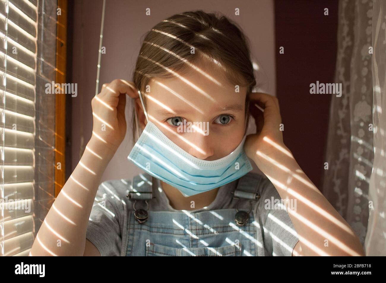 Little girl is sitting on the windowsill and trying to put protective disposable mask on her face during self-isolation at home because of Coronavirus Stock Photo