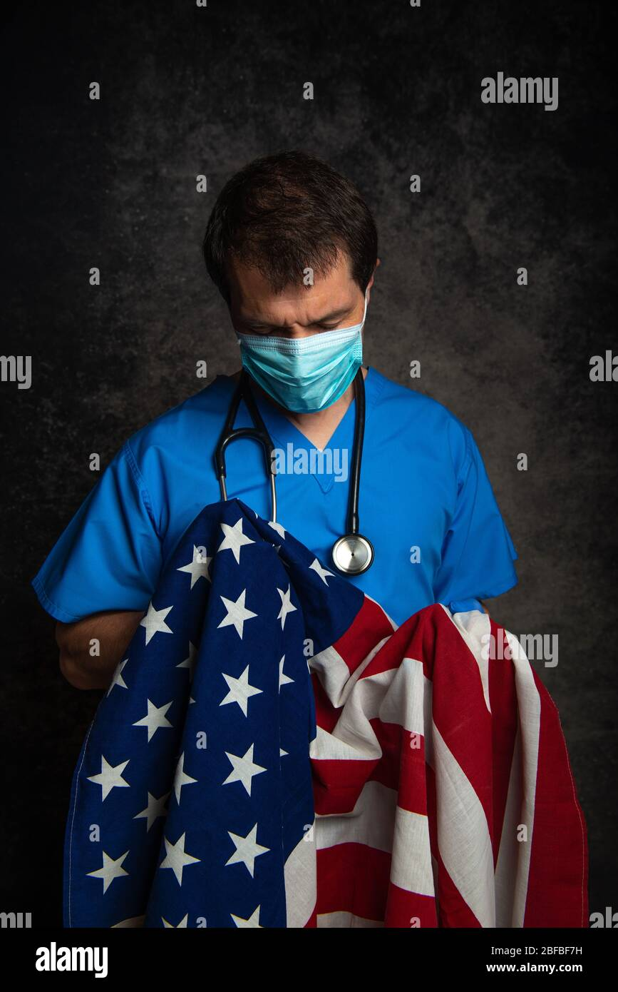 Sad/pensive, male doctor in blue hospital scrubs with face mask and stethoscope, holding the Stars & Stripes American flag close to his chest. Stock Photo