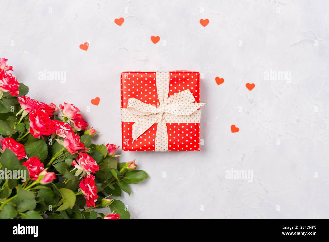 Red gift box and red roses on white background with red heart confetti. Christmas present, valentine day surprise, birthday mother's day concept. Flat Stock Photo