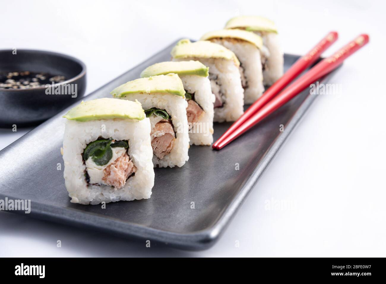 Sushi Roll With Avocado Wrap Grilled Salmon Philadelphia Cheese And Green Onions Black Container And Red Chopsticks Stock Photo Alamy