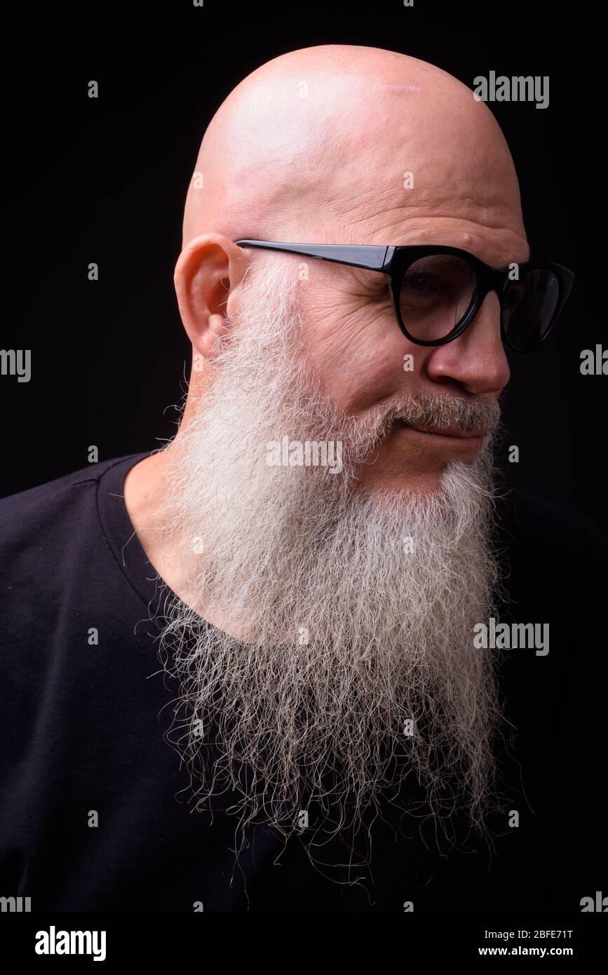 Mature bald bearded man against black background Stock Photo