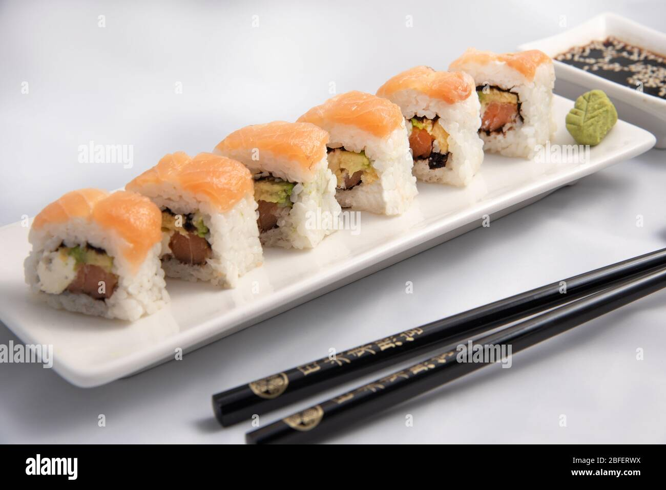 Sushi Roll With Pink Salmon Wrap Grilled Salmon Philadelphia Cheese And Avocado White Container And Black Chopsticks Stock Photo Alamy