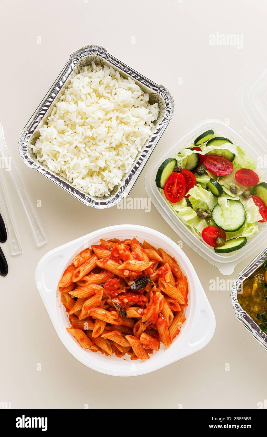 takeaway food in disposable containers: rice, vegetable curry, Italian pasta with tomato sauce and fresh healthy salad. Stock Photo