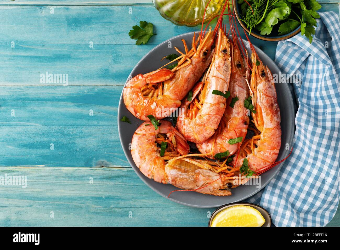 Top view of turquoise color dining table with cooked red prawns and ingredients Stock Photo