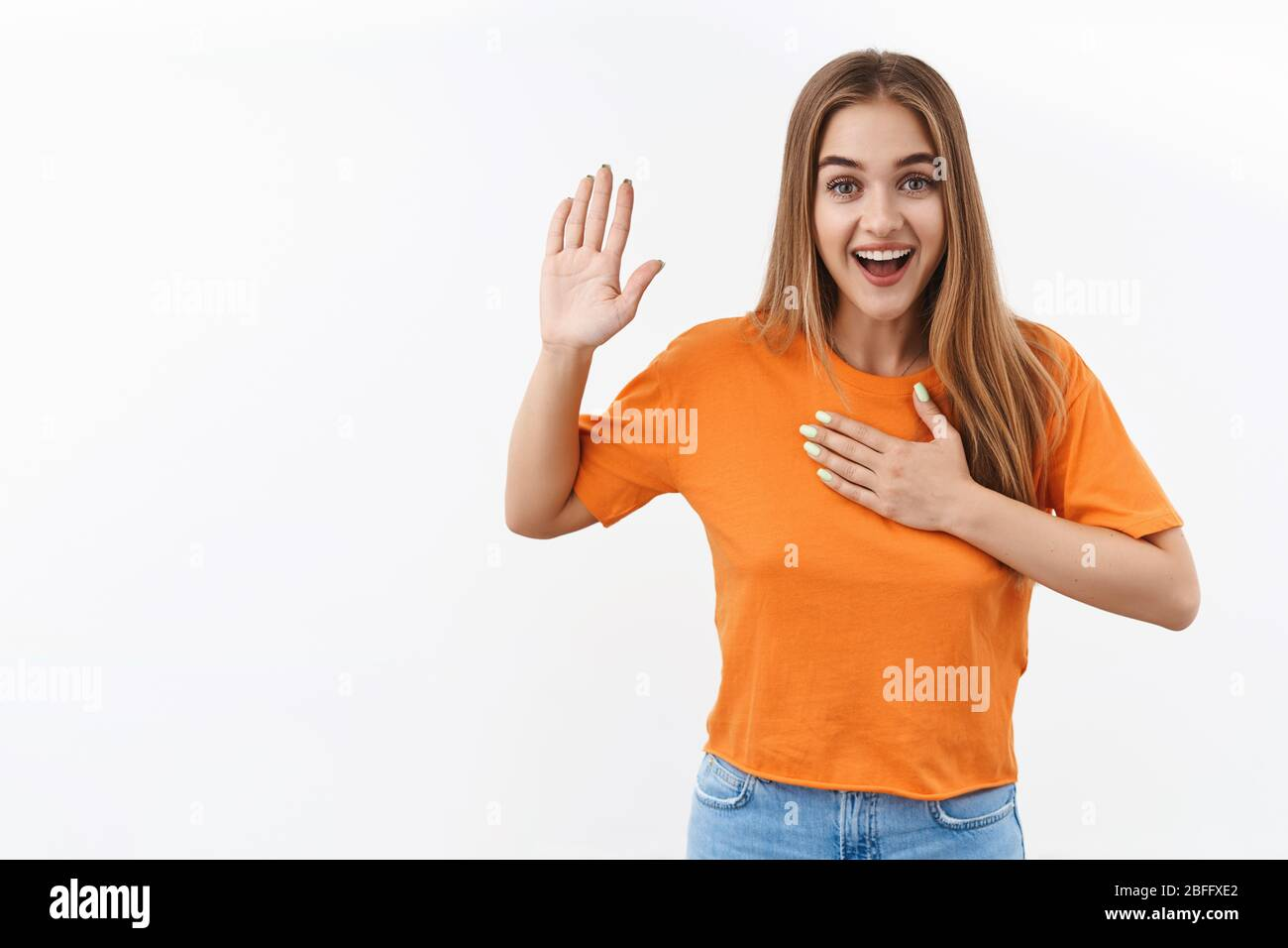 I swear, promise you not regret. Portrait of happy, sincere blonde girl raising one arm and hold hand on heart as give oath, pledge, telling truth, wa Stock Photo