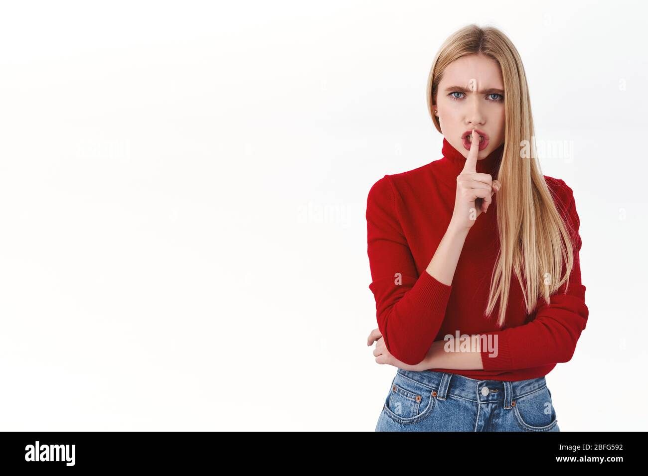 Employee, management and confident women concept. Angry serious blond female shushing, shhh with finger over lips, frowning mad tell be quiet, need si Stock Photo