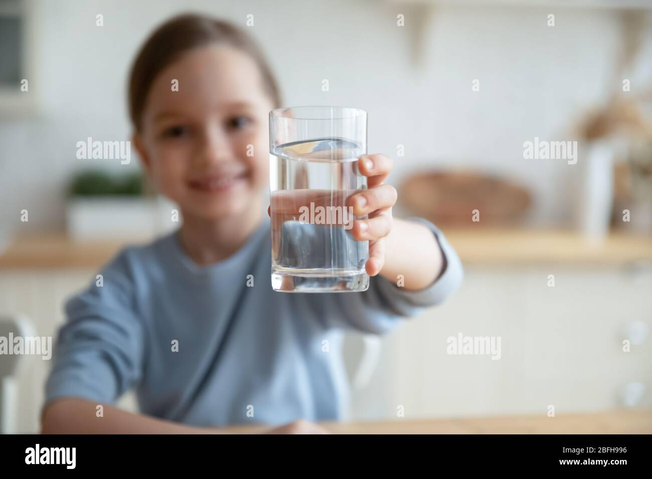 Little girl offer clean mineral water for body refreshment Stock Photo