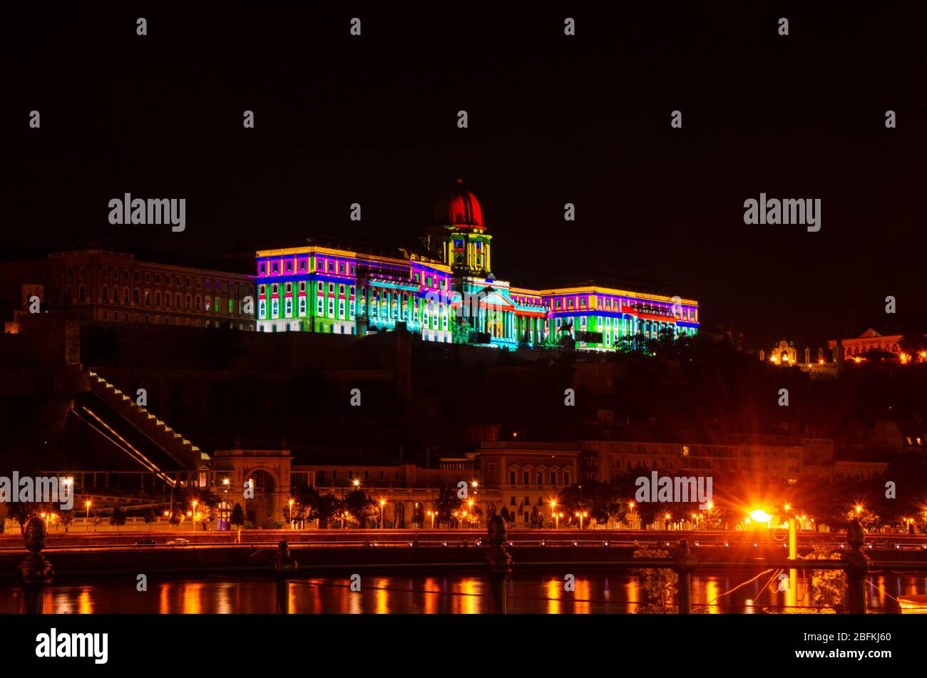 Hungarian National Gallery building lit in vibrant colours at night, the architecture standing out in the dark at Budapest, Hungary Stock Photo