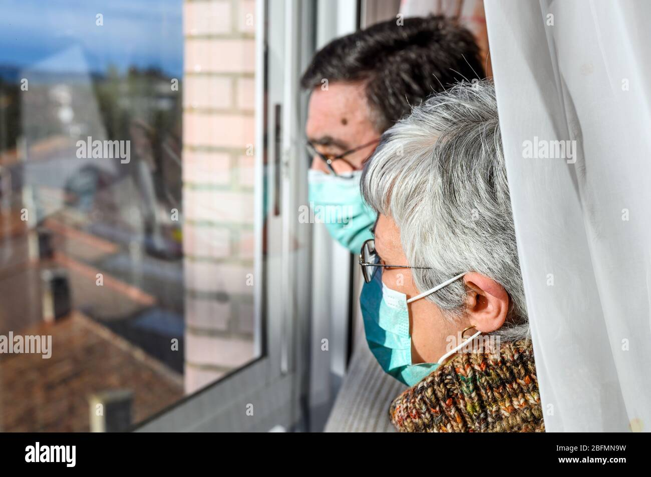 senior couple, with protective face masks, at home looking through the window. Concept of coronavirus quarantine stay home and social distancing. Lockdown people. elderly and retired lifestyle . Stock Photo