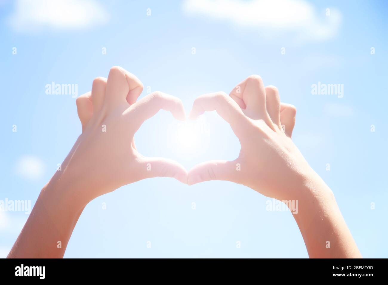 Female hands in heart shape on blue sky background Stock Photo