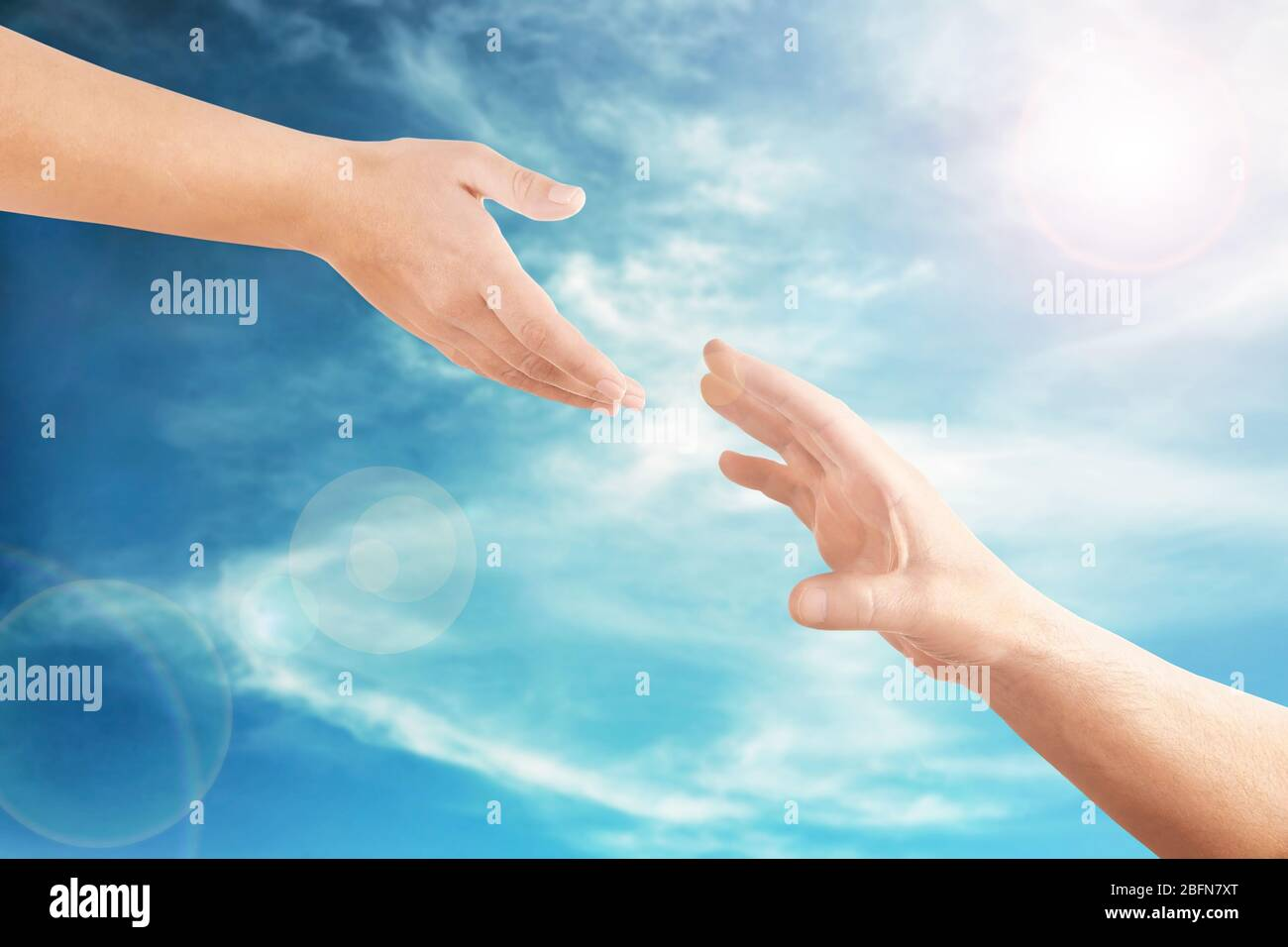 Female and male hands reaching to each other on sky background. Help and care concept. Stock Photo