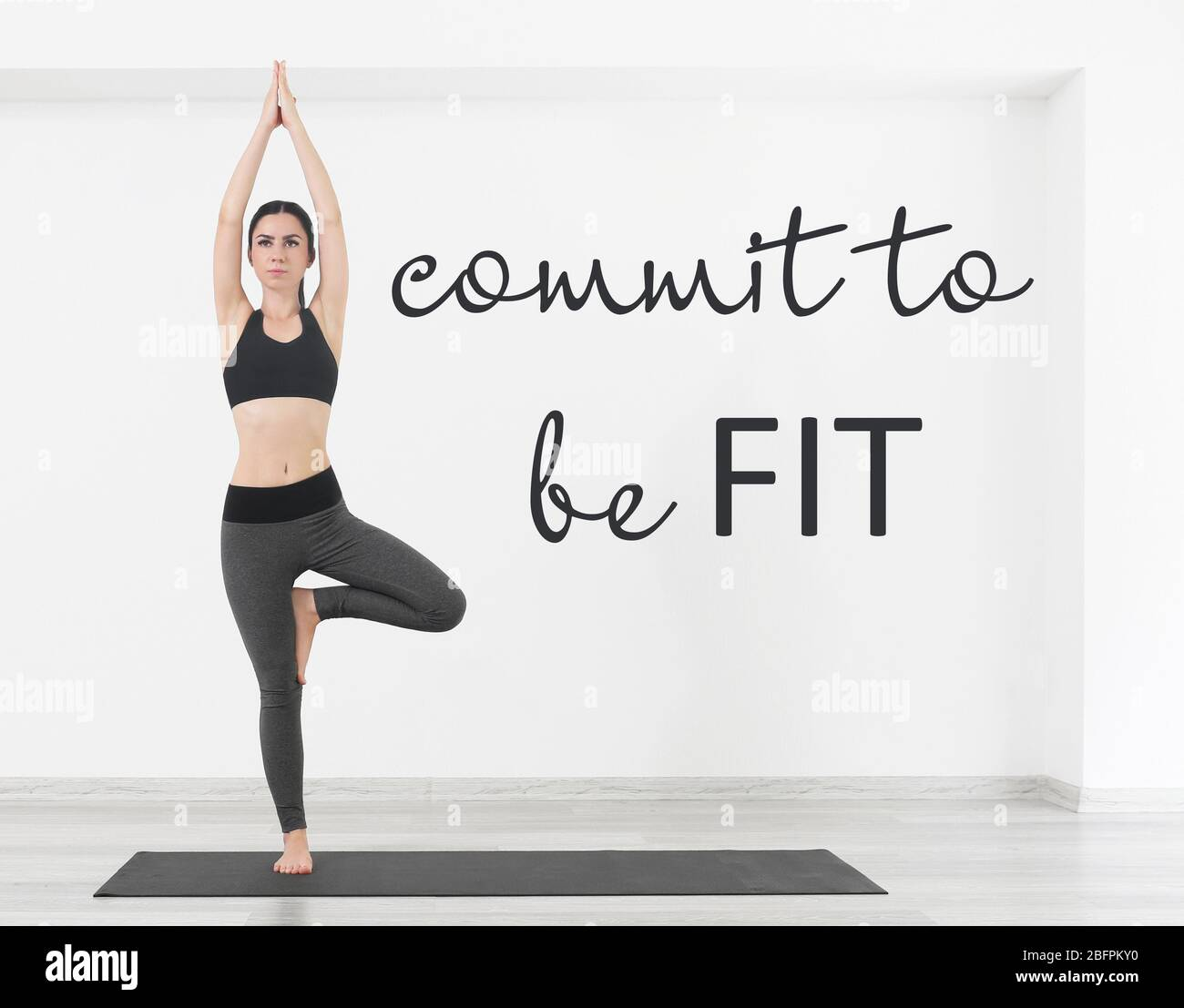 Fitness Quotes Text Commit To Be Fit And Young Woman Practicing Yoga On White Wall Background Stock Photo Alamy
