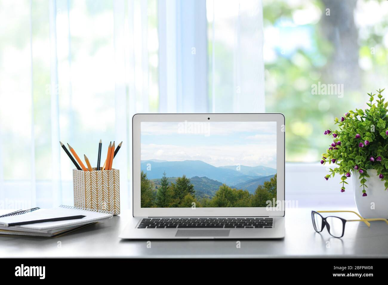 Workplace With Laptop And Wallpaper Of Landscape On Screen Stock Photo Alamy