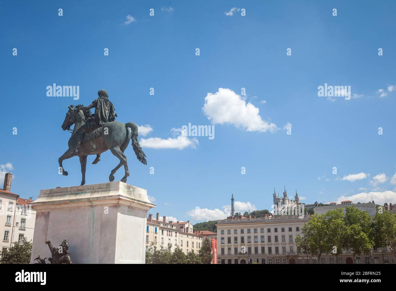 Roi Louis XIV statue on the Place Bellecour Square, in downtown Lyon, with the Basilique Notre Dame de Fourviere Church in background in summer.  pict Stock Photo