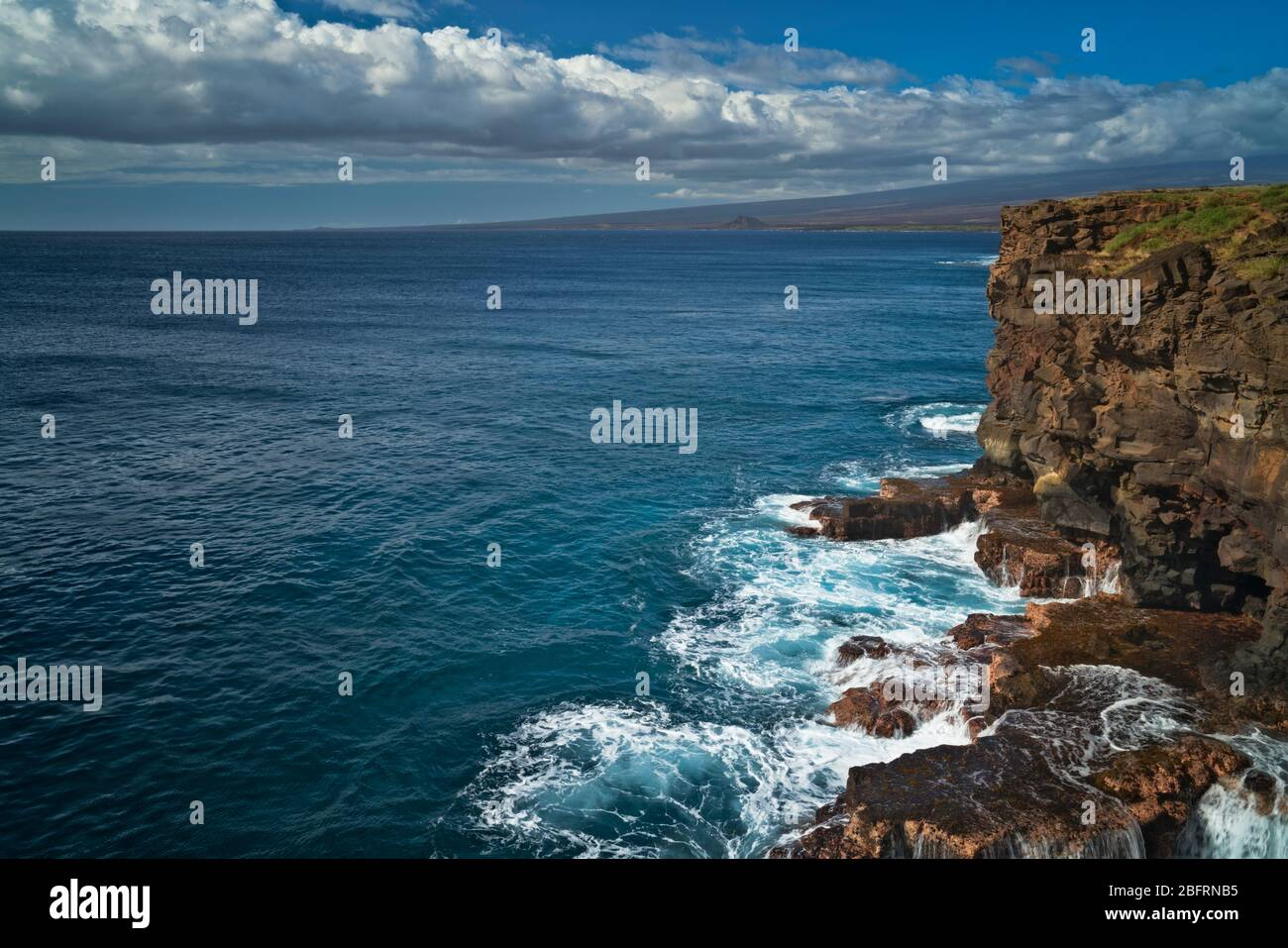Waves crash against the volcanic cliffs at South Point on the Big Island of Hawaii and the southern most location in the United States. Stock Photo