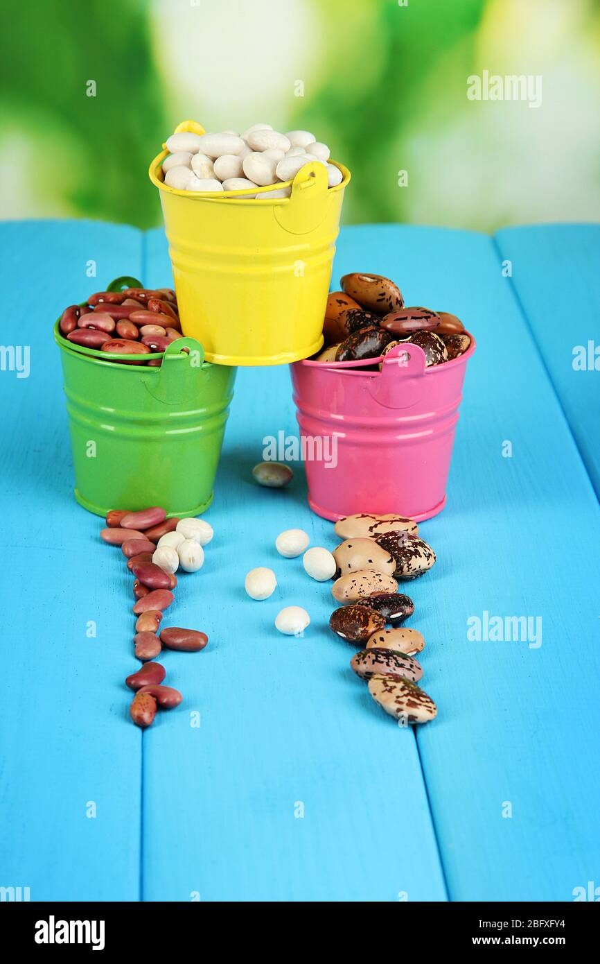 Different Types Of Beans In Colored Buckets On Blue Wooden Table On Natural Background Stock Photo Alamy