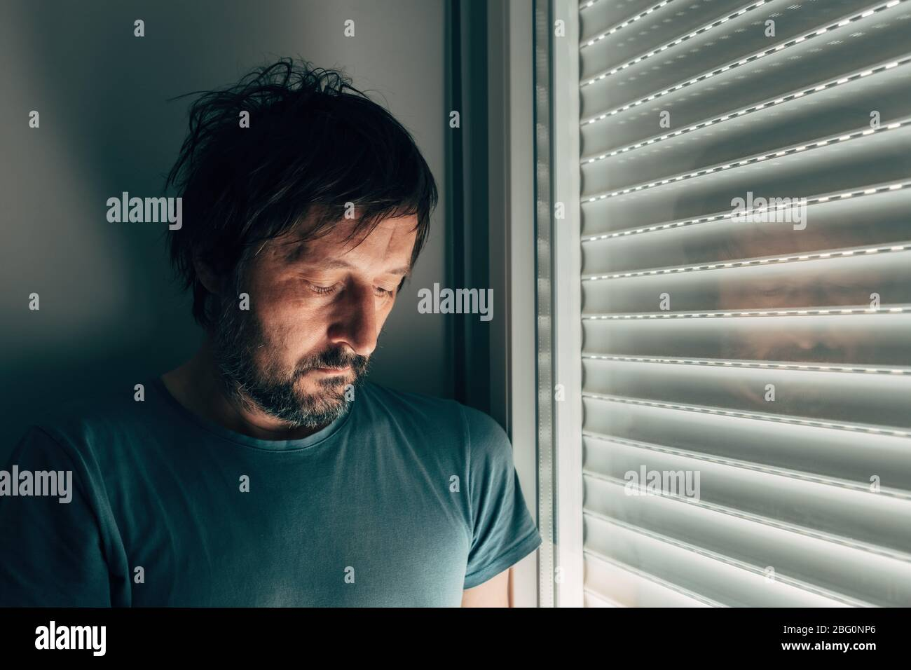 Sulking man by the window with shutters rolled down, portrait of disappointed male person Stock Photo