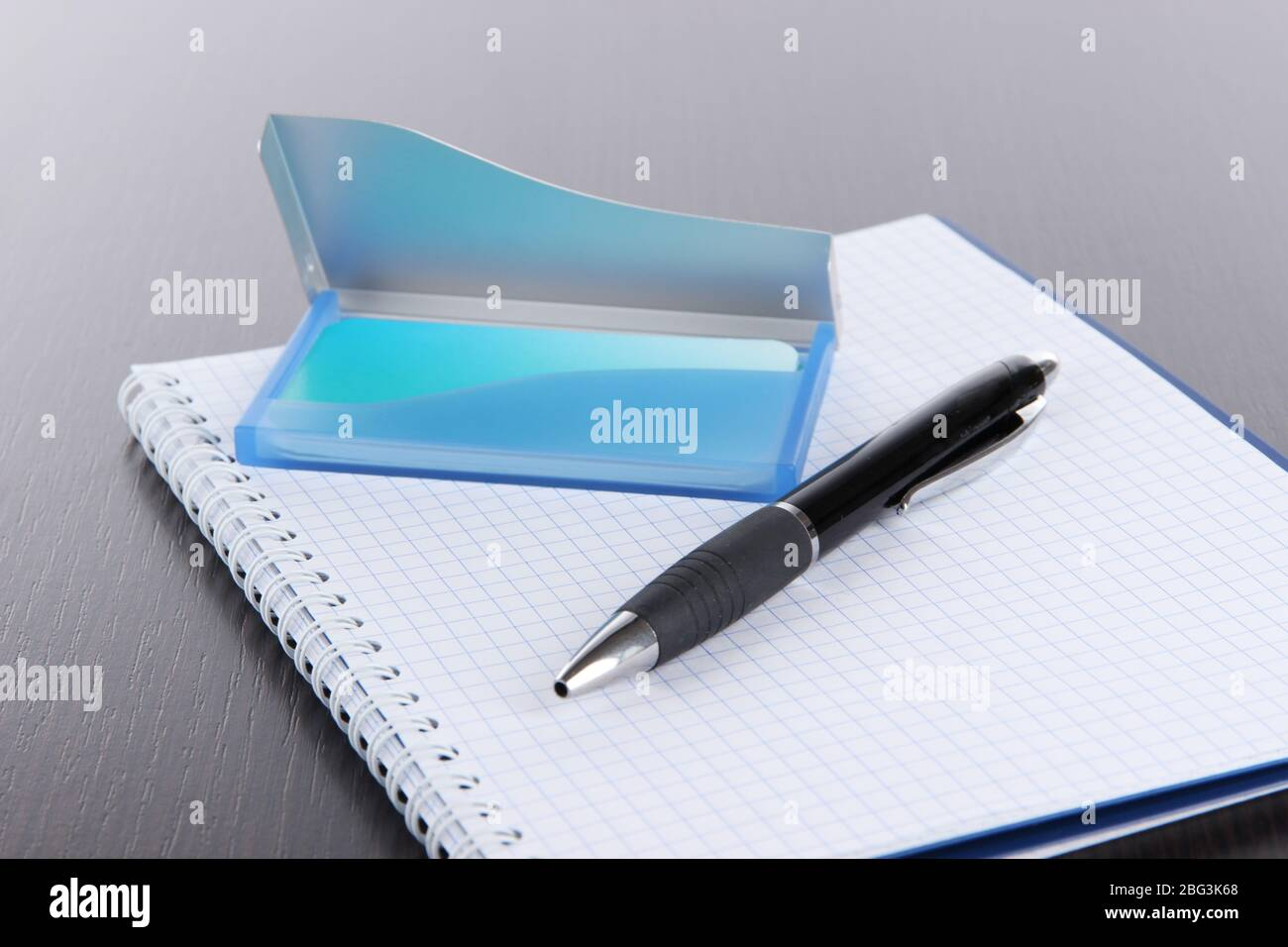 Blue business card holder, notebook and pen close-up Stock Photo