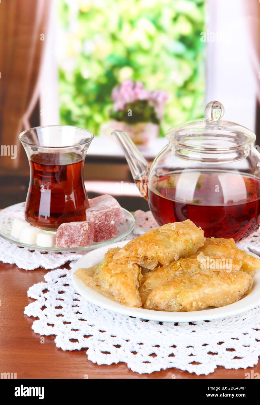 Sweet baklava on plate with tea on table in room Stock Photo