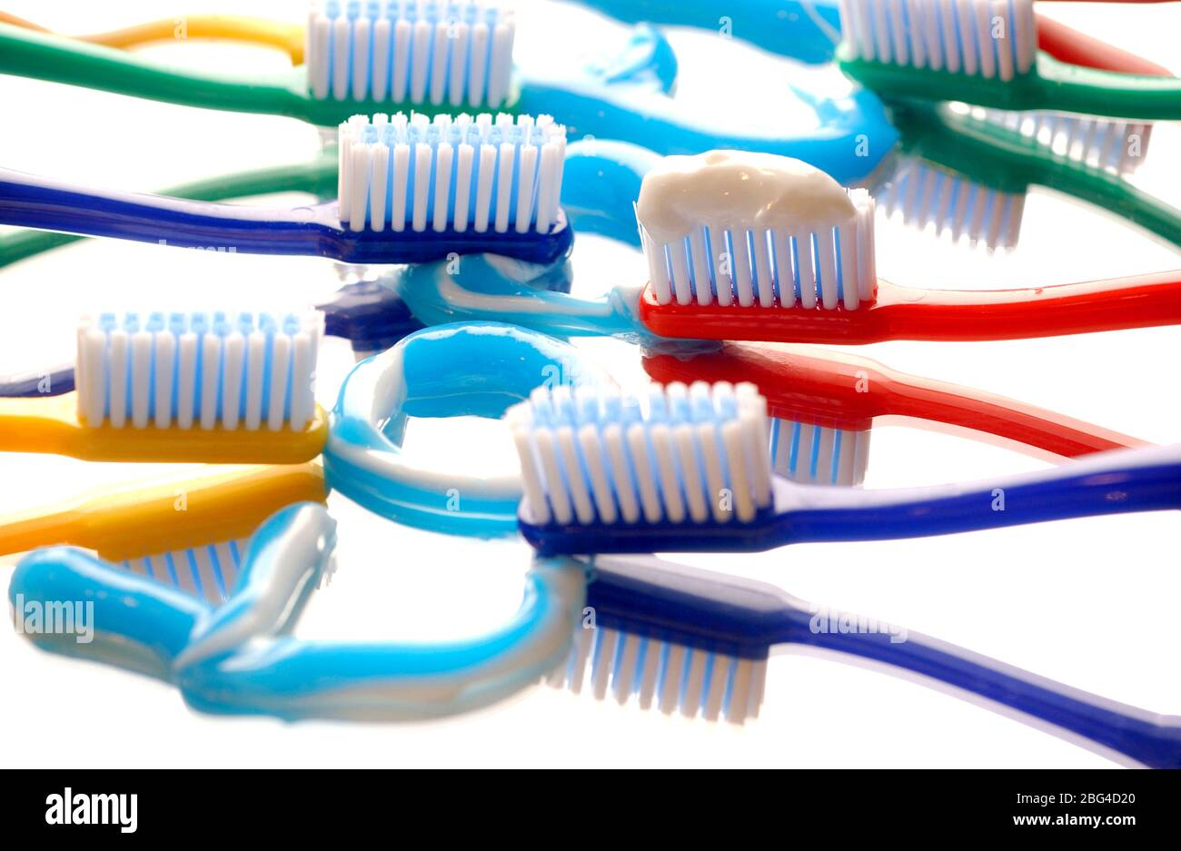 "The word ""tooth"" is written out using toothpaste on a mirrored surface, surrounded by multicouloured toothbrushes. Stock Photo"