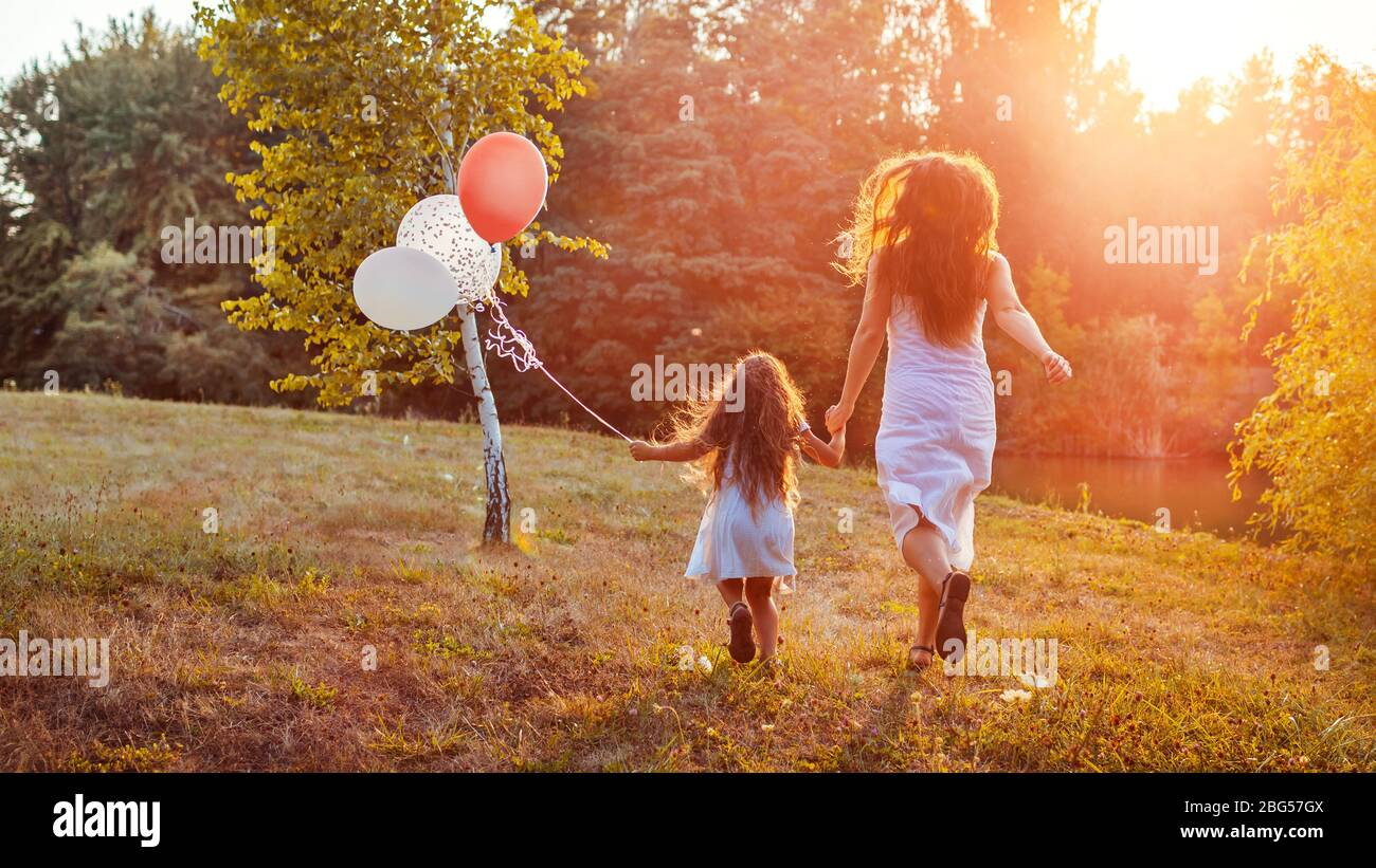 Mother's day. Little girl running with mother and holding baloons in hand. Family having fun in summer park Stock Photo