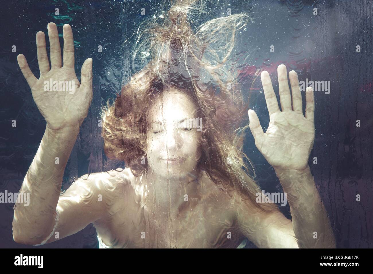 Woman under water. A young woman is trapped in a water surface. Hands resting on. summer feeling. Underwater. Stock Photo