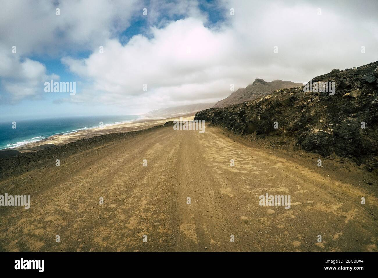 Off road ground view straight way and wild sand beach at the en in background - concept of adventure and alternative nature around lifestyle - tourism Stock Photo
