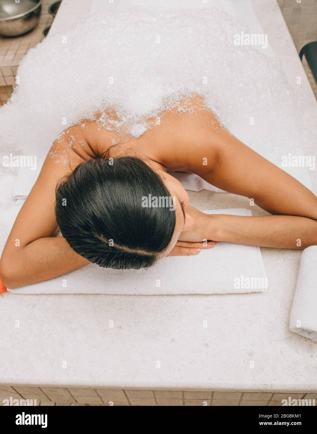 Soap massage of a beautiful woman in a hammam, top view. Procedures in the Turkish bath improves the skin and stops the aging process Stock Photo