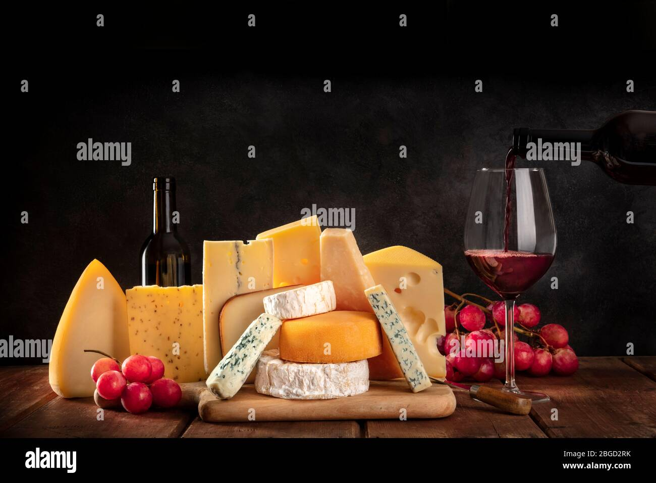 Cheeses with grapes and pouring wine, a side view on a dark background with copy space Stock Photo