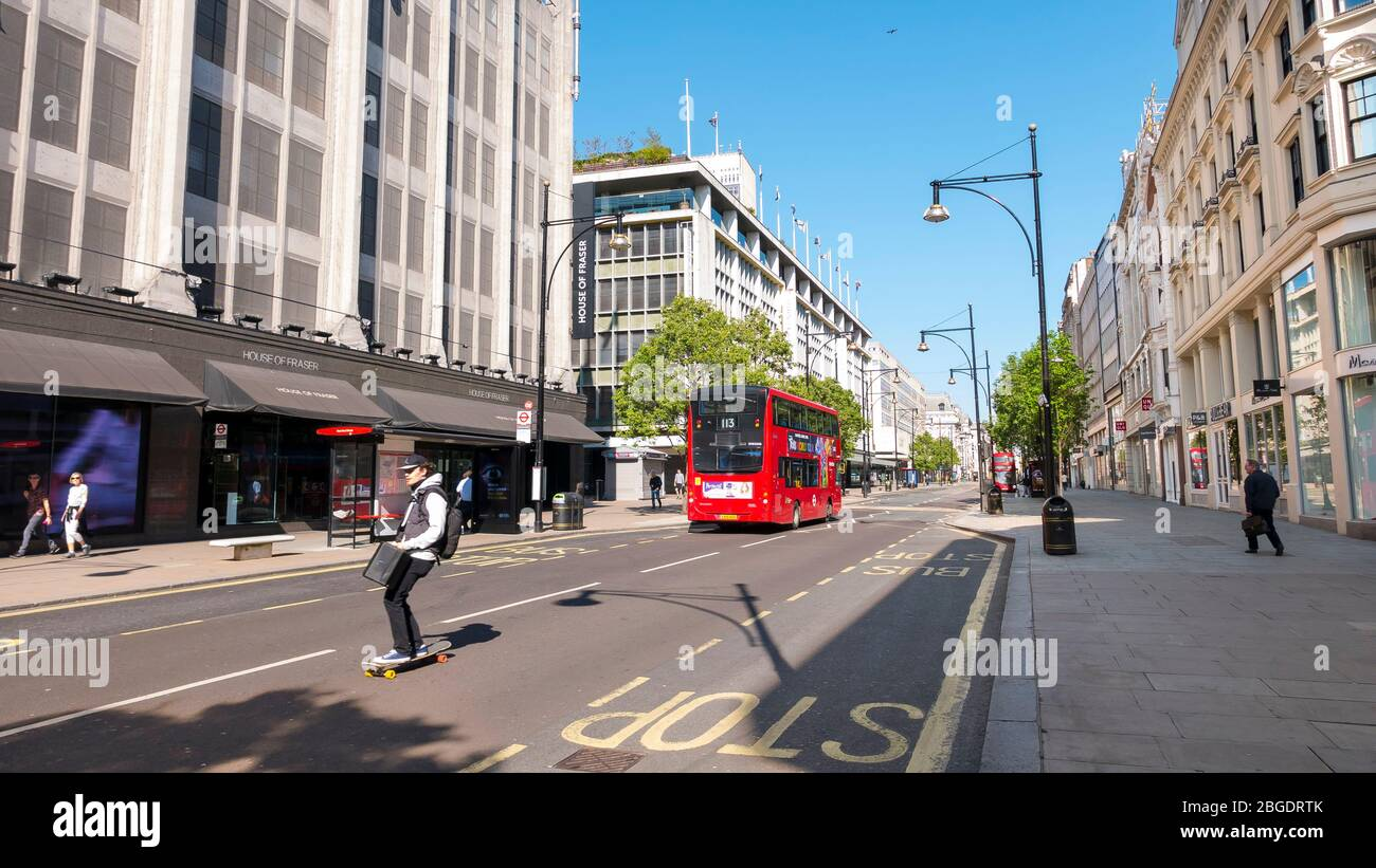 Skate boarder in Oxford Street, Coronavirus Pandemic in London  April 2020. No people , a few buses  in the streets, all shops closed during lockdown Stock Photo
