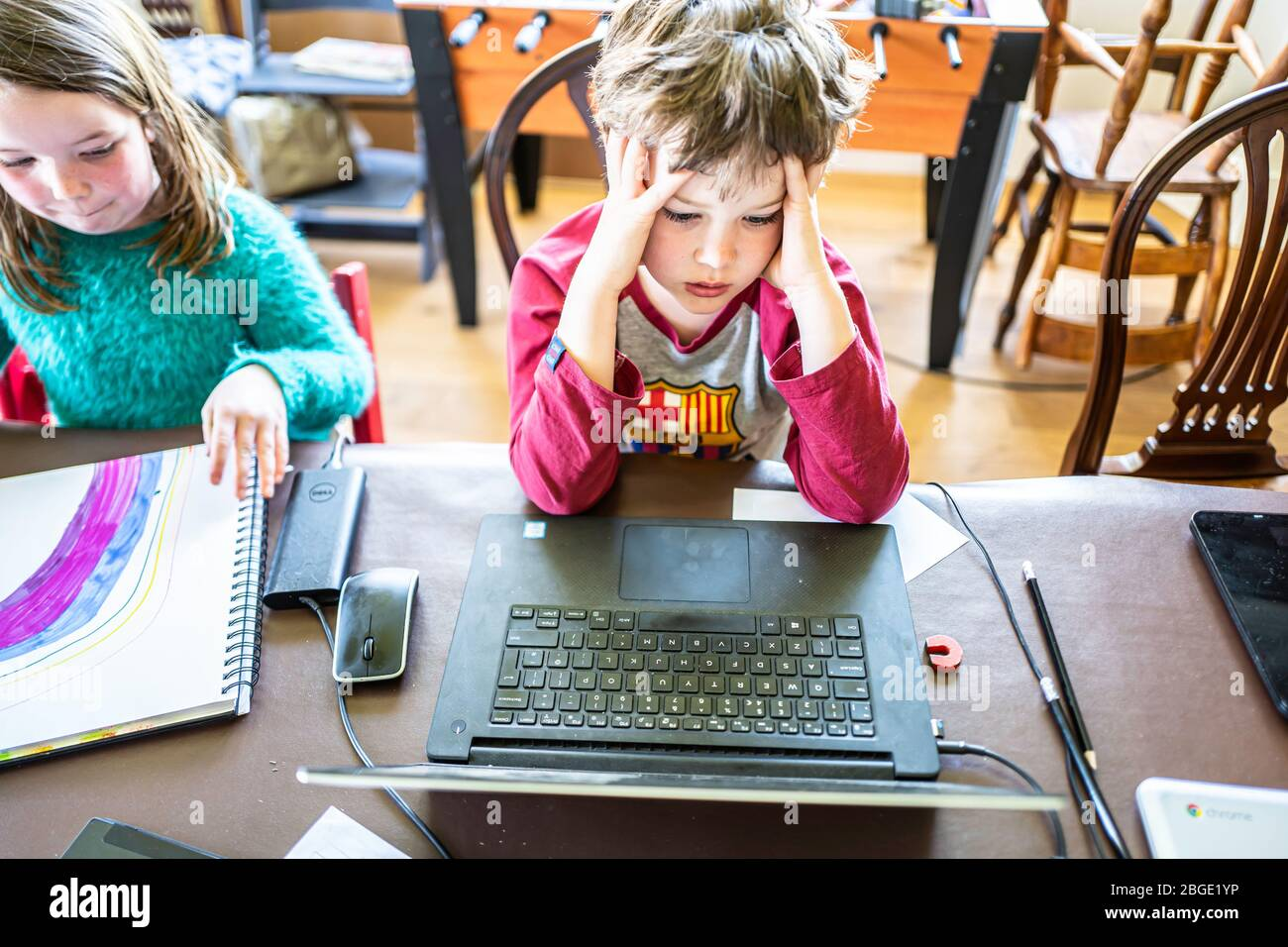 Camptown, Jedburgh, Scottish Borders, UK. 15th April 2020. Max and Lizzie Scott, 9 and 7, are being taught online by their school St. Mary's of Melros Stock Photo