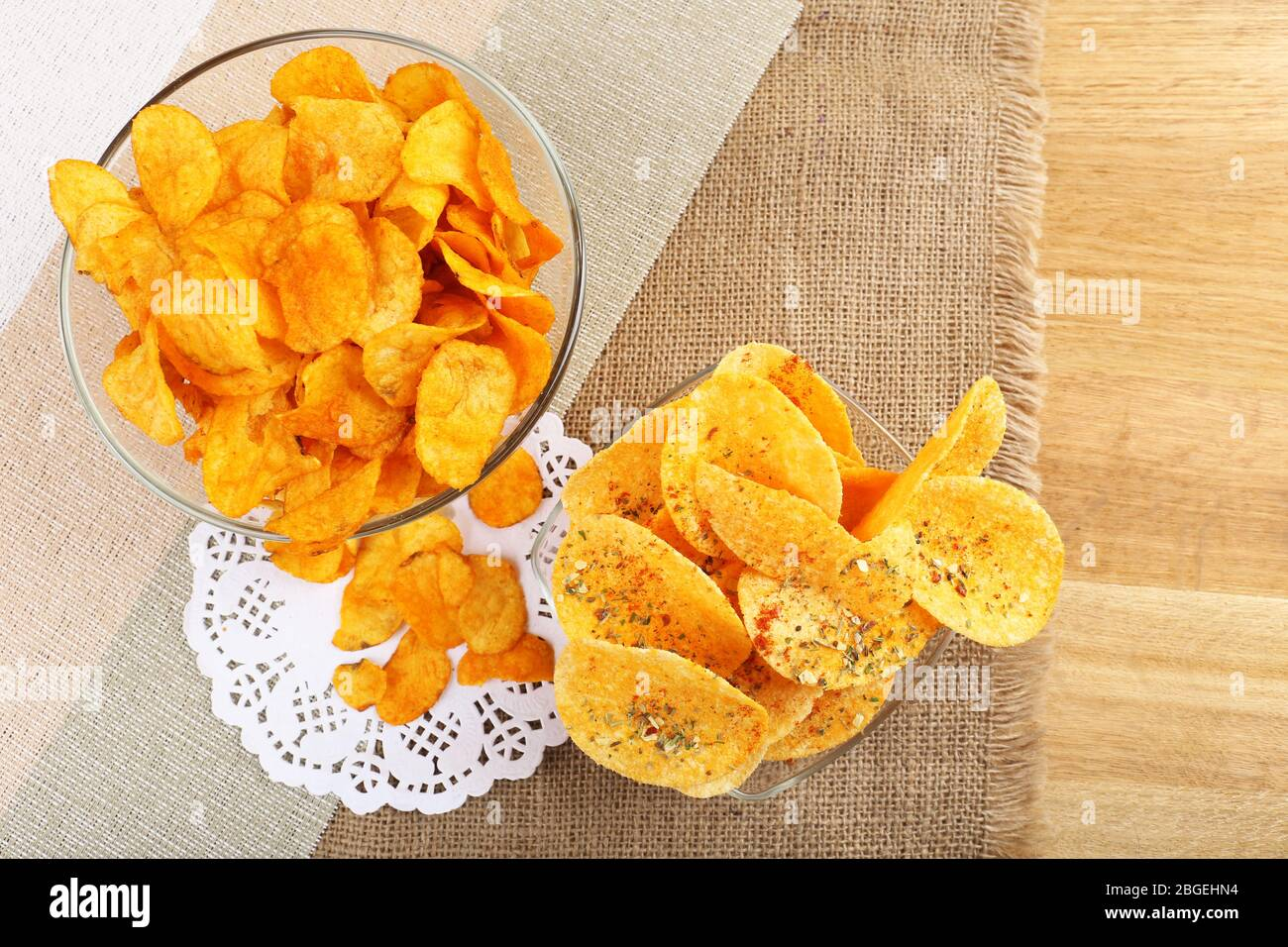 Homemade potato chips in glass bowls on table Stock Photo