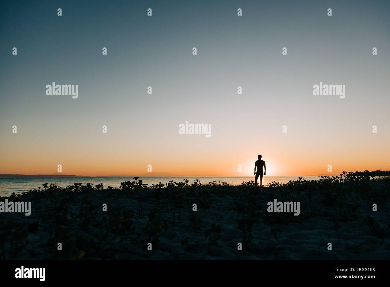 Silhouette of a man enjoying sunset on the beach Stock Photo