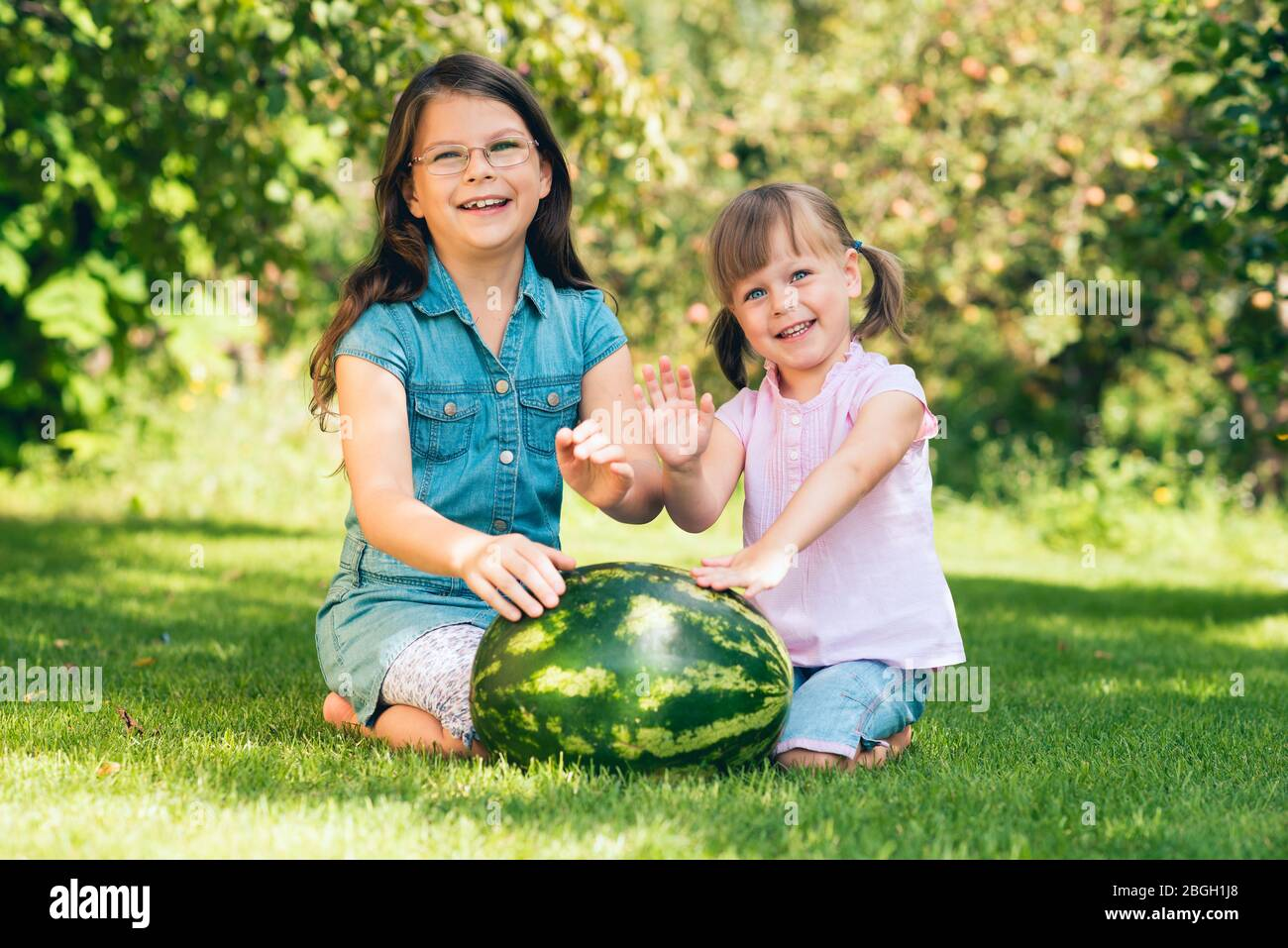 Little toddler girls squatting by the large watermelon on the lawn in the summer garden - spending free time together concept - shallow depth of field Stock Photo
