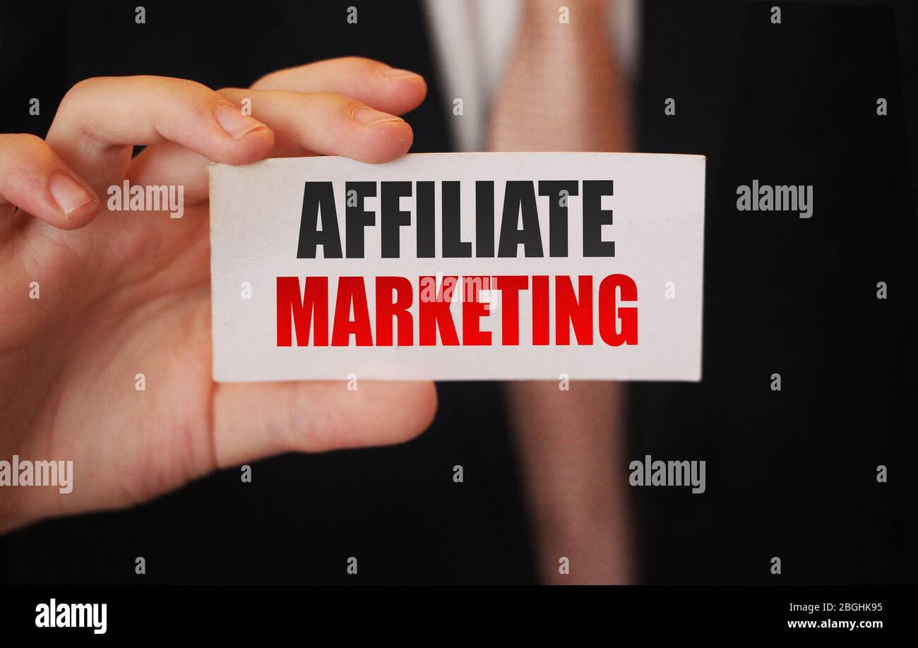 Affiliate Marketing words in card in businesman hand. Refer a friend business model concept Stock Photo