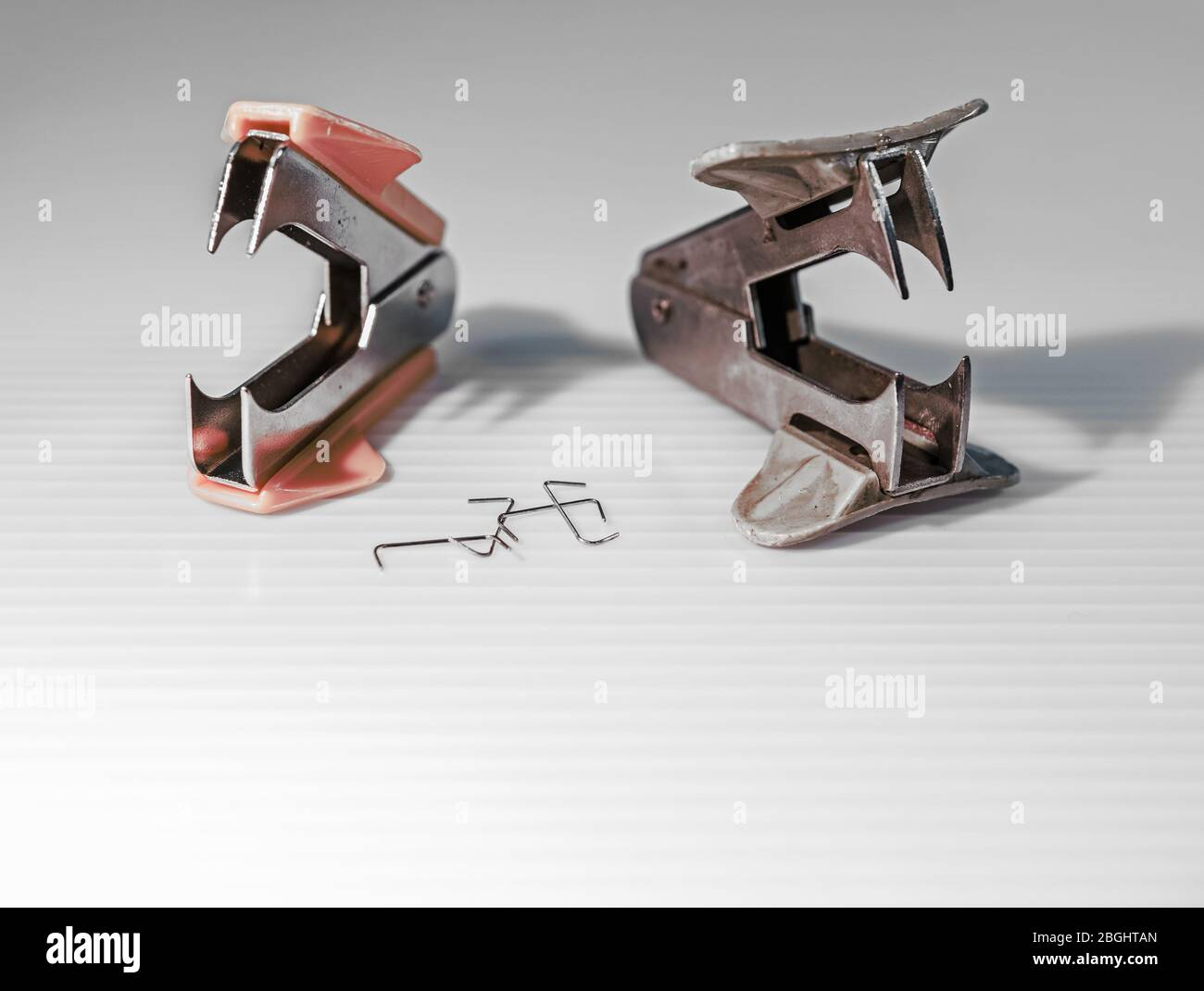 Staple removers that look like predatory monsters ... next to their victims:  removed staples... Stock Photo