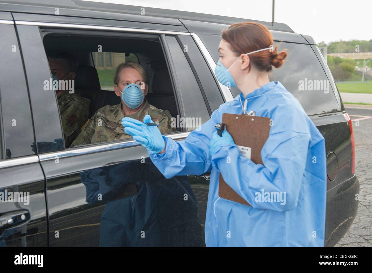 Texas Army National Guard Spc. Amanda Patton, assigned to the Medical Readiness Clinic Detachment, performs a mock drive-through COVID-19 screening with Major General Tracy R. Norris, the Adjutant General of Texas on March 18, 2020. Drive-through COVID-19 screening centers allow the public to receive COVID-19 tests while limiting physical contact to better protect healthcare workers and others waiting to be tested. (U.S. Army National Guard Photo by Andrew Ryan Smith/Released) Stock Photo