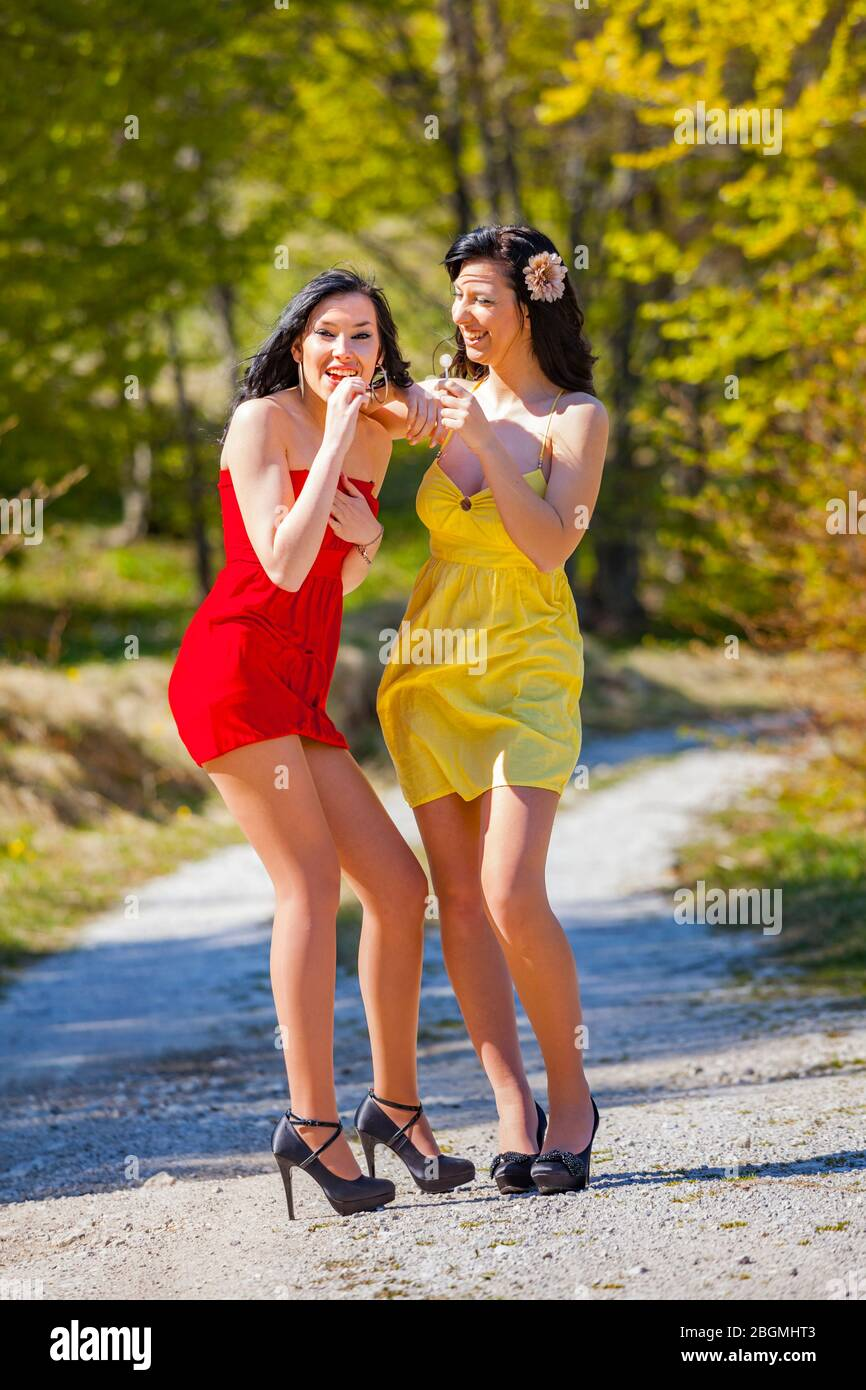 Girlfriends enjoying outdoor sunlight together chatting conversation talking standing countryroad country-road holding lollipops lollipop laughing Stock Photo