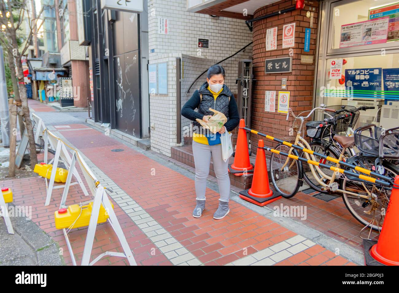 An Asian woman in black sweater is wearing protection mask on her face in the street of Tokyo, Japan February 8,2020 Stock Photo